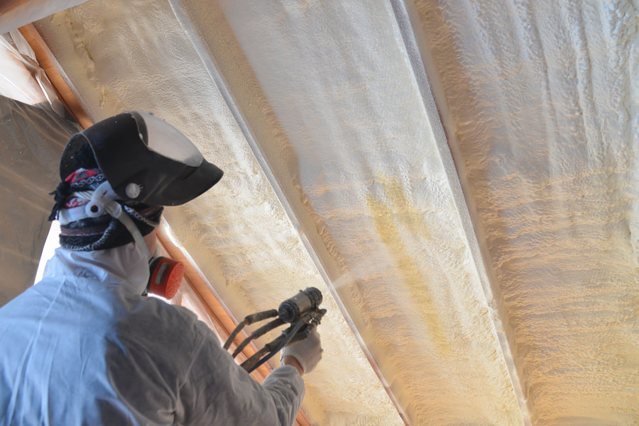 man wearing his protective suit while spraying foam in the attic